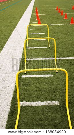 Yellow Banana hurdles and .orange cones set up for jumping and running on a green turf field