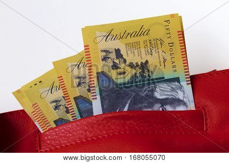 Australian fifty dollar notes in a red leather bag.