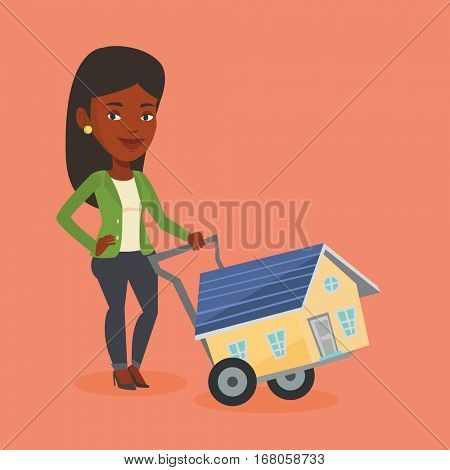 Happy african-american woman pushing a shopping trolley with a house. Young woman buying house. Woman using shopping trolley to transport a house. Vector flat design illustration. Square layout.