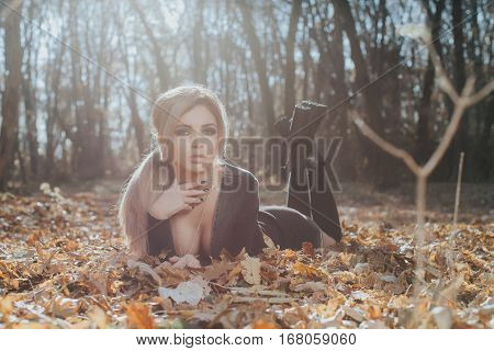 Beautiful woman posing in the forest lies down on the leaves