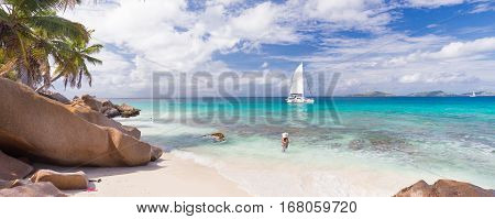 Woman wearing long floral summer dress and beach hat on Anse Patates beach on La Digue Island, Seychelles. Summer vacations on picture perfect tropical beach concept.