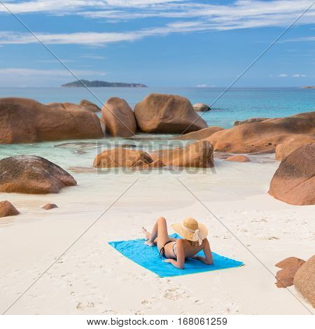 Woman wearing black bikini and beach hat, sunbathing at Anse Lazio beach on Praslin Island, Seychelles. Summer vacations on picture perfect tropical beach concept.