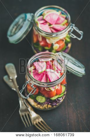 Healthy take-away lunch jars. Vegetable and chickpea sprout vegan salad in glass jars over dark scorched wooden background, selective focus. Clean eating, vegetarian, raw food, dieting concept