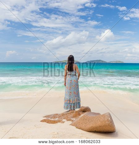 Traditinaly dressed local woman wearing long floral summer dress and hat looking at sea on Anse Patates beach, La Digue Island, Seychelles. Summer vacations on picture perfect tropical island concept.