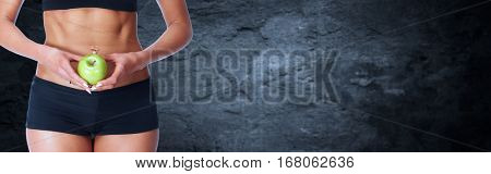 Young fitness woman abdomen with apple.
