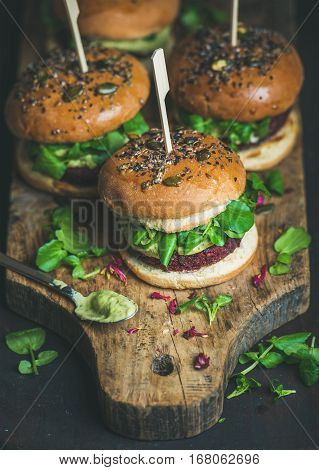 Healthy vegan burger with beetroot and quinoa patty, arugula, avocado sauce, wholegrain bun on rustic wooden board over dark wooden background, selective focus. Clean eating, detox, vegan food concept