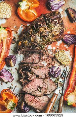 Cooked Roastbeef meat with roasted vegetables and herbs in metal baking tray, top view, vertical composition. Slow food concept