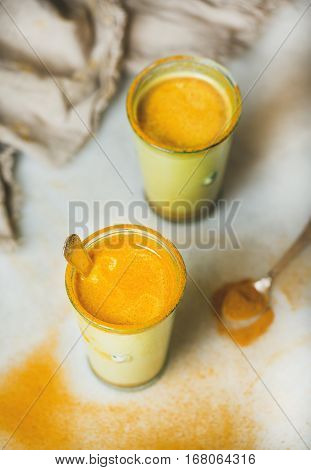 Golden milk with turmeric powder in glasses over grey marble background. Health and energy boosting, flu remedy, natural cold fighting drink. Clean eating, dieting, detox, weight loss concept