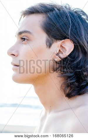 Close-up portrait of shirtless young handsome guy with long black hair emotionlessly looking away