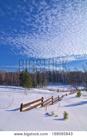 wooden fence on a snow - covered field