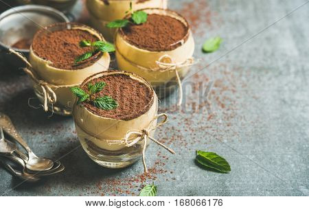 Homemade Italian dessert Tiramisu served in individual glasses with mint leaves and cocoa powder over grey concrete background, selective focus, copy space