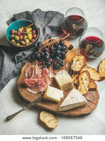 Wine and snack set. Variety of cheese, olives, prosciutto, roasted baguette slices, grapes on wooden board and glasses of red wine over grey marble background, selective focus