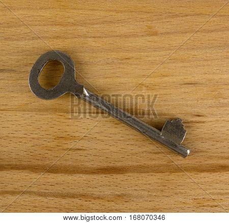 Old keys lie on a wooden background
