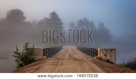 Low cloud and darkened skies.  Single point perspective, surreal coloured subdued light from summer storm over a single lane, steel & timber bridge spanning a narrow passage in a lake.