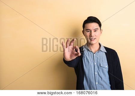 young man give you a gesture of okay, shot at studio yellow background
