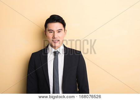 young Asian business man, closeup portrait on studio yellow background