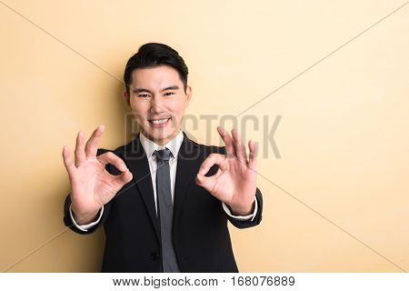 young Asian business man give you a gesture of okay, closeup portrait on studio yellow background