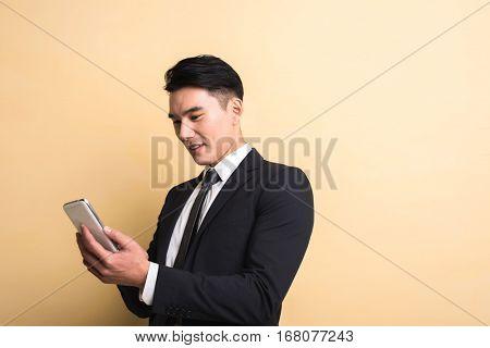 Asian business man use smart phone, closeup portrait on studio yellow background