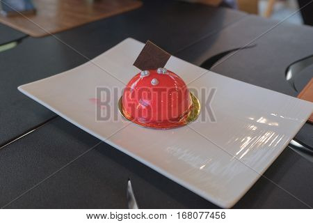 Strawberry cake ball with shinny skin and chocolate silver ball on top on wooden chopping block ready to eat / Strawberry ball cake
