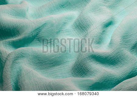 Pale turquoise chiffon fabric background. Wrinkles are like waves of the sea or the hills.