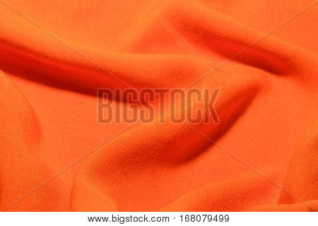 Orange cotton textile factory fabric texture waves and folds background.