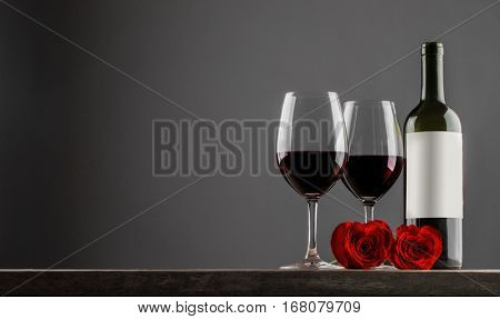 Two glasses and bottle of red wine, heart shaped roses, Valentine day
