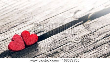 Two small wooden red hearts on old cracked wood background