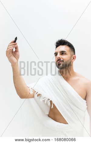 Muslim man posing as ready for Hajj visiting Kaaba in Mecca writing copy space for your text