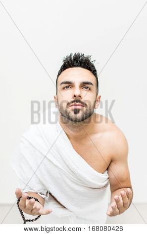 Muslim man posing as ready for Hajj visiting Kaaba in Mecca