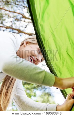 Young blonde woman pitching a tent.