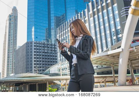 Asian Business Woman use Wireless Smartphone in Modern City as Digital Technology Concept