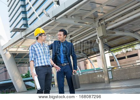 Young Male Architects Discussing with Businessman at Construction Site as Business Industrial Communication Development Concept.