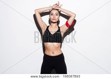 Beautiful young sportswoman with armband listening to musing using earphones over white background