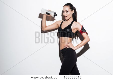 Happy alluring young woman athlete standing and pouring water from bottle on herself over white background
