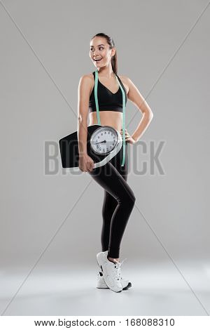 Full length of happy young woman athlete with weighing scale and measuring tape over gray background