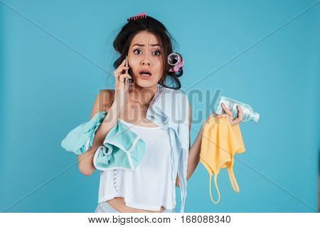 Image of sad young lady with hair curlers isolated over blue background talking by phone and holding clothes