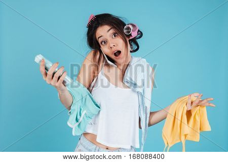 Photo of confused young woman with hair curlers isolated over blue background talking by phone and holding clothes