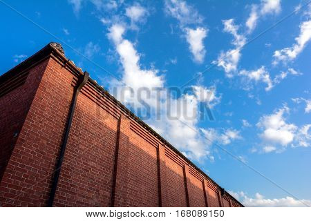 Brick building wall under blue sky with clouds