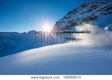 Freerider skier jumping in fresh powder snow in beautiful Alpine landscape. Fresh powder snow, blue sky on background.