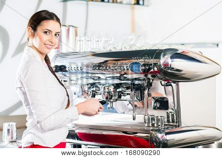 Young Caucasian waitress looking at camera while using an automatic coffee machine