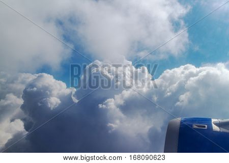 airplane's wing over a blue and cloudy sky