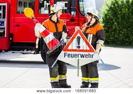 Female fire fighters in emergency operation setting up attention sign