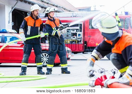 Fire fighter connecting hoses in front of fire engine