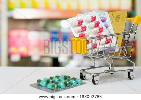 Shopping trolley with blisters of medical capsule pills and credit card with Blurred medicines shelves in pharmacy shop background