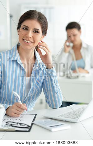 Portrait of a young female office worker, using laptop