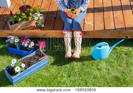 Woman gardener wearing wellington boots have a coffee break while working in the garden, she is sitting on patio wooden floor