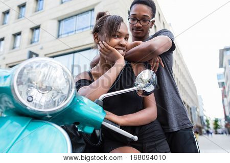 African American young couple leaning on blue scooter in the city