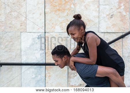 Funny young man carrying his girlfriend on back while descending stairs