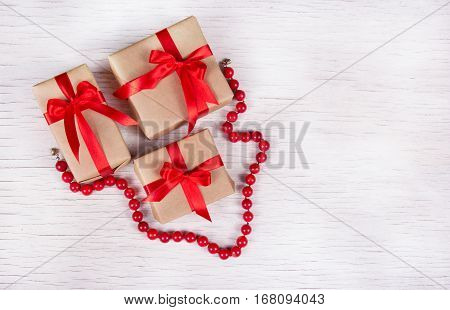A stack of gift boxes and red coral necklace on a white wooden background. Holiday concept. Copy space