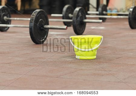 Sport background. Gymnasium with barbells and a bucket with magnesium